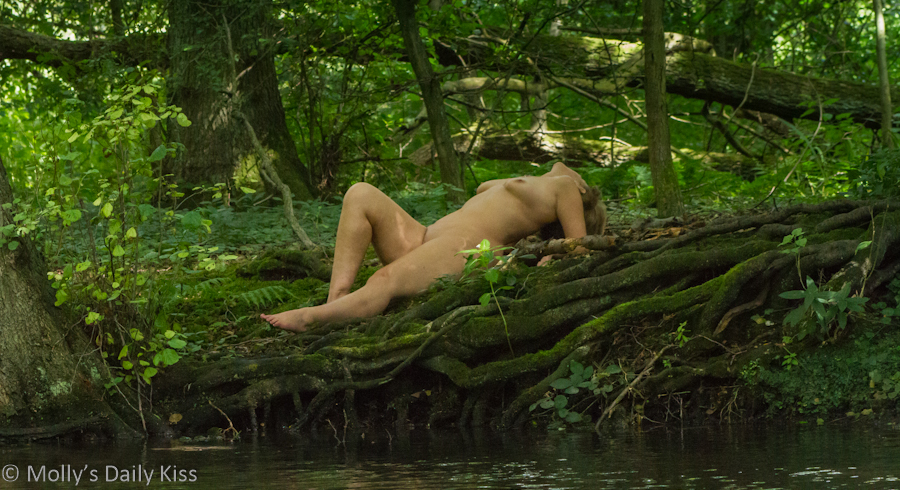 Woman laying naked on the banks of a stream