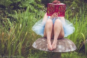 Molly in blue fairy tutu sitting on stone toadstool reading fairy story book