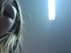 Half face of woman looking down at the viewer with ceiling light behind her head