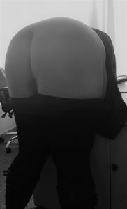 Woman bent over desk with her bum exposed