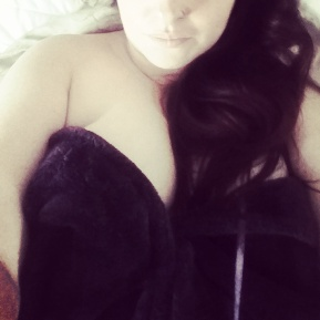 Woman with long black hair snuggled up in bed. Sex positivity