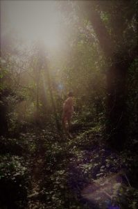 Nude of large woman in sharft of sunlight in woodlands