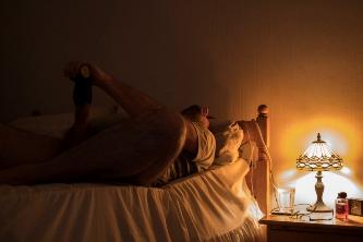Man laying on bed in lamplight using male masturbator