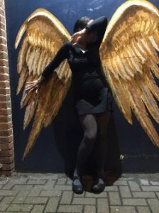 Woman in black dress in front of golden wings