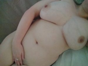woman with large breasts laying on the bed
