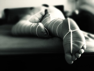Woman laying face down on bed bound in white rope with it passing between her toes