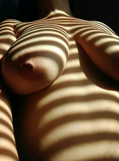 Shadow lines from blinds on naked womans body