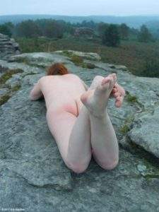 Nude woman laying on top of rocks