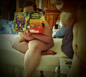 Young woman sitting naked on bed with bunches in her hair hiding behind dinsaur sticker book