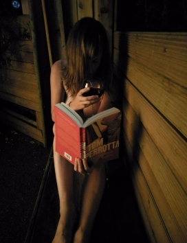 Woman sitting in naked in the garden at night reading a book