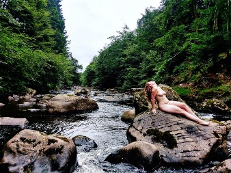 Woman laying naked on huge rocks in river