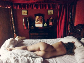 Woman laying naked on four poster bed with nude men reflected in the mirror