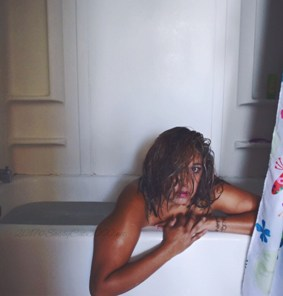 Woman sitting in bath with smeared makeup