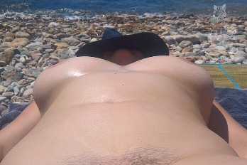woman laying in the sun on the beach naked