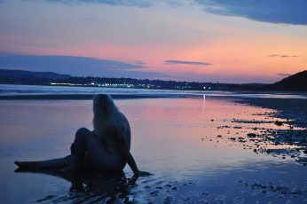 woman sitting naked on the shore with dusty pink sunset behind her