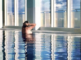 Woman topless in indoor swimming pool with light shining throught the windows