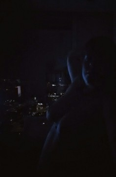 Woman nude in dark office with city skyline behind