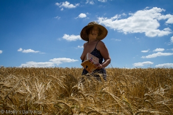 Molly standing in field of wheat wearing large sunhat and book