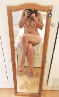 Woman sitting naked on bed taking selfie in long mirror