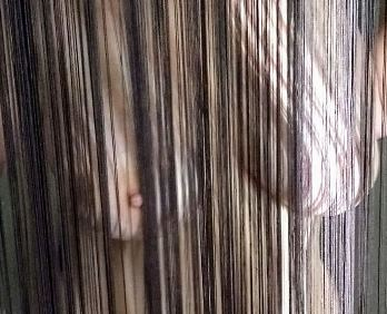 Looking through string curtain to nude woman
