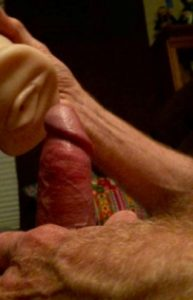 Man with erect penis holding male masturbator over it