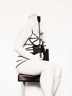 woman sitting on black chair wearing black body harness and holding whip