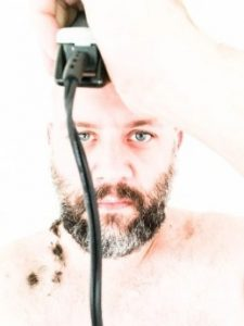 Man with piecring blue eyes shaving his head with clippers