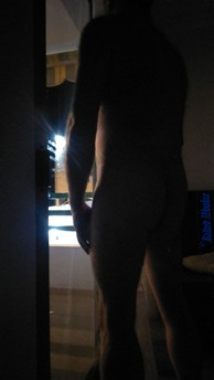 Dark figure of naked man standing in the doorway