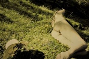 Woman laying on mossy green grass nude