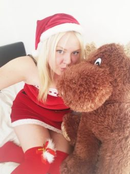 Woman in sexy santa outfit with giant teddy