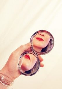 Woman holding companct mirror with reflection of her red lips showing in the mirror
