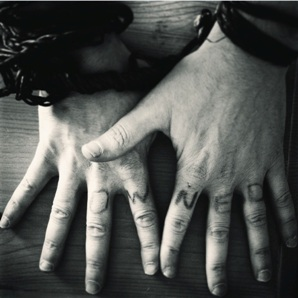 Man with chains around his wrists and the word owned written across his knuckles