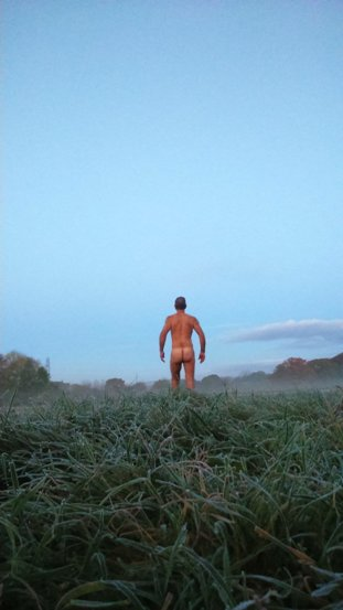 Man walking naked away from the camera with frost covered grass in the foreground and bright blue skies