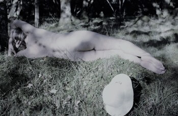 Woman laying in sunshine naked on the grass with vintage paled out tones