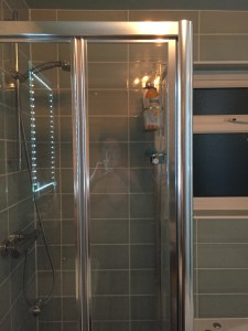 Ghostly image of nude woman in glass shower door
