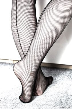 Woman legs and feet in fishnet stockings