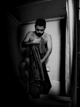 Man stepping out of the show holding towel in black and white