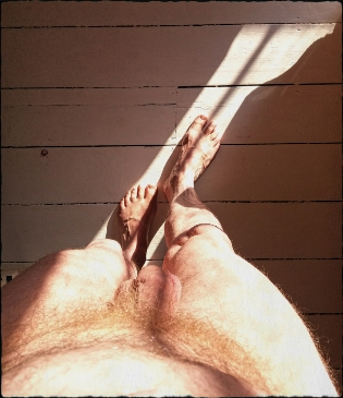 Looking down naked mans body to feet in sunlight