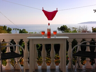 bottle of wine on table with two glasses with red bikini bottoms hanging over the top looking out over the ocean