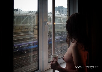 Woman standing topeless at window watching trains go past