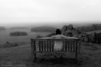 Nude woman sitting on bench on top of a hill overlooking the view