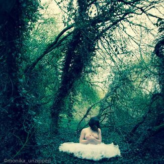 Topless woman sitting in woodland with big shite tulle skirt around her