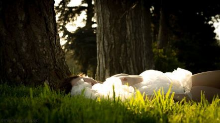 Woman laying in sunlight with breasts out wearing white fluffy dress