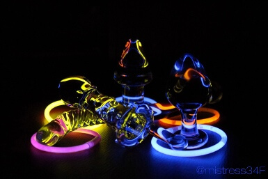 selection of glass sex toys illuminated by glow in the dark bracelets