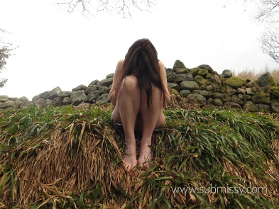 Woman sitting on grass bank naked with her head bowed down on her knees