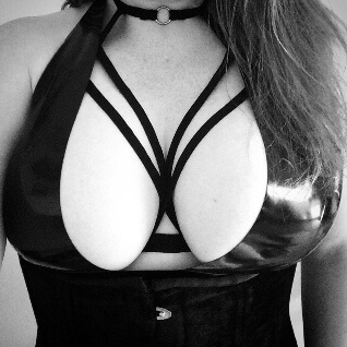Woman in black bralet with straps across her chest