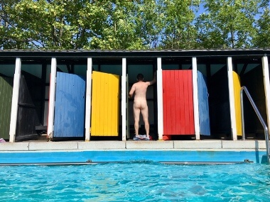 Nude Man in outdoor changing room with other colourful doors shut either side of him