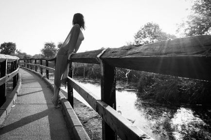 Woman in see-through top leaning over the railing of a bridge
