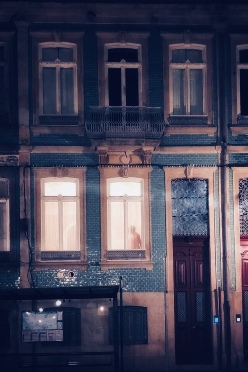 town house at night with man light up in the window