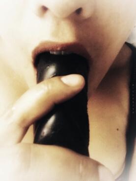 woman sucking on black dildo